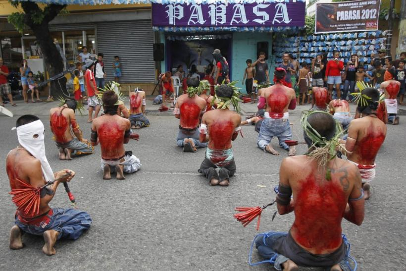 Hooded barefoot penitents performing self-flagellation to atone for their sins pray in front of a chapel in San Fernando, Pampanga in northern Philippines