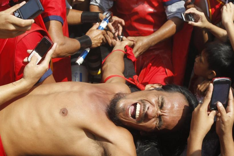 Filipino penitent Bobby Gomez grimaces while being nailed to a wooden cross during a reenactment of Jesus Christ's crucifixion on Good Friday in Barangay Cutud