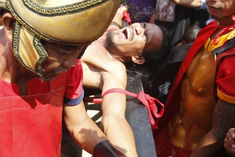 Filipino penitent Gomez grimaces while being nailed to a wooden cross during a reenactment of Jesus Christ's crucifixion on Good Friday in Barangay Cutud