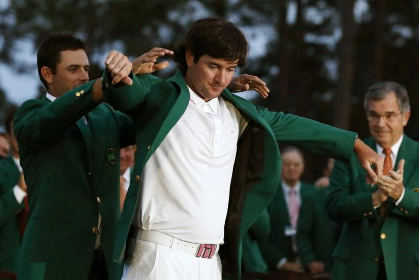 Bubba Watson gets his green jacket from 2011 Masters Tournament champion Charl Schwartzel as Augusta National Golf Club Chairman William Porter Payne, right, applauds the 2012 champ on Sunday in Augusta, Ga.