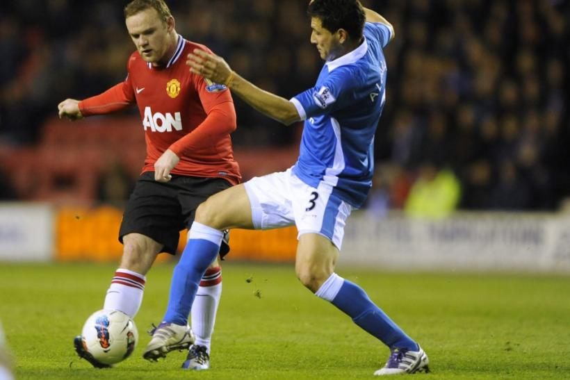 Wigan Athletic's Alcaraz challenges Manchester United's Rooney during their English Premier League soccer match at the DW Stadium Wigan