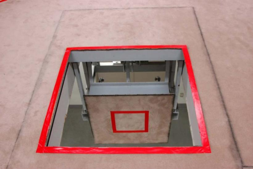 A trap door marked with a red square where an inmate stands, is seen opened at an execution chamber at the Tokyo Detention Center.