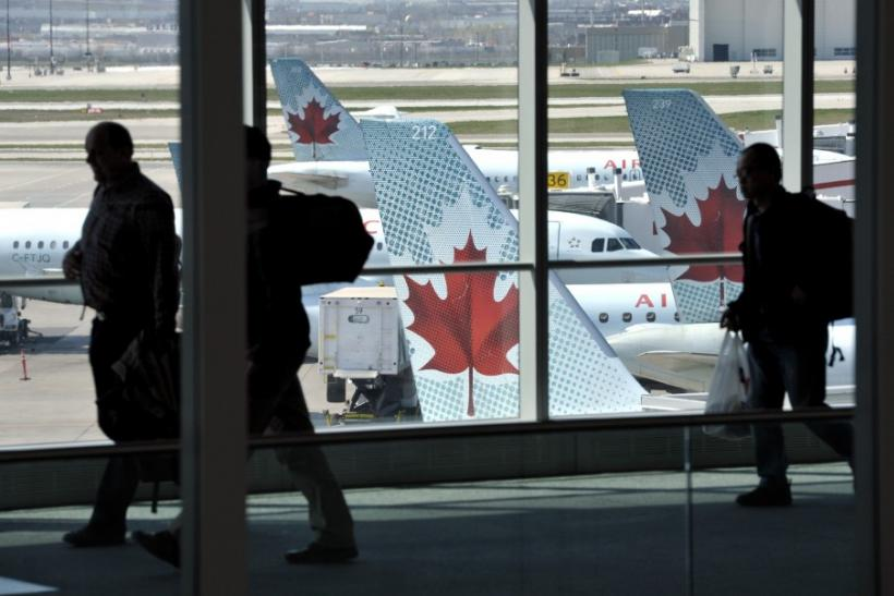 Passengers walk past Air Canada planes on the runway at Pearson International Airport in Toronto.