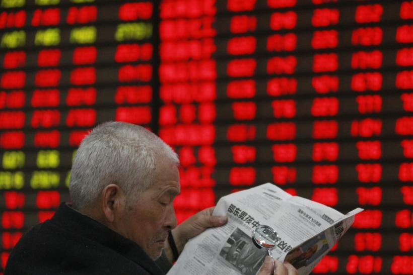 An investor reads a newspaper with a magnifying glass in front of an electronic board showing stock information at a brokerage house in Huaibei, Anhui province April 5, 2012.