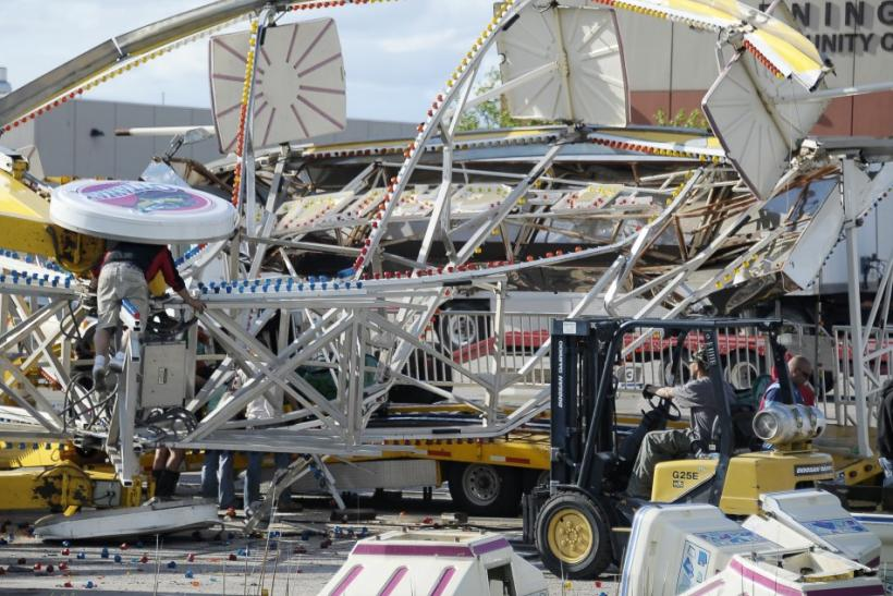 Workers try to dismantle and untangle a Ferris wheel that was flipped over by a tornado in southern Wichita