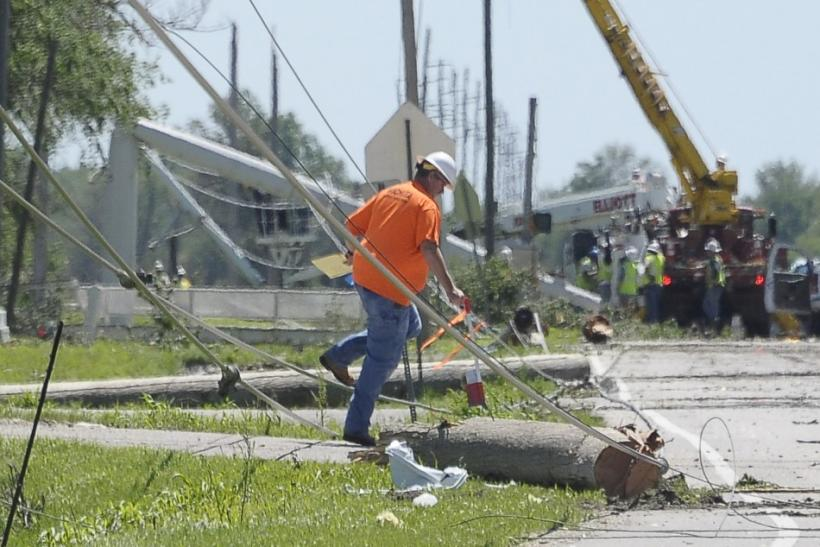 A worker walks near a downed power line caused by tornado damage in the southern area of Wichita, Kansas