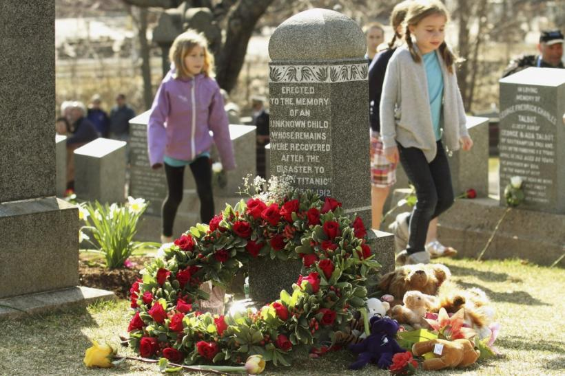 Children walk past the grave of an unknown child from the Titanic sinking at the Fairview Lawn Cemetery in Halifax