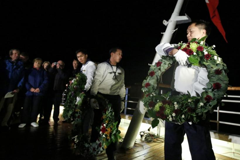 Crew members carry wreaths to be thrown into the sea during a service of remembrance aboard the Titanic Memorial Cruise in the western Atlantic Ocean