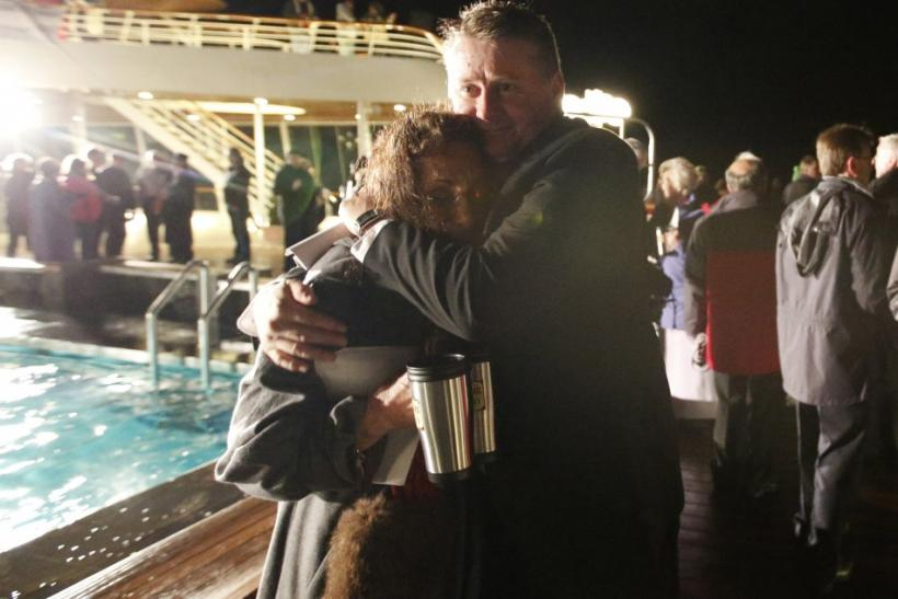 Passengers embrace after a service of remembrance aboard the Titanic Memorial Cruise in the western Atlantic Ocean