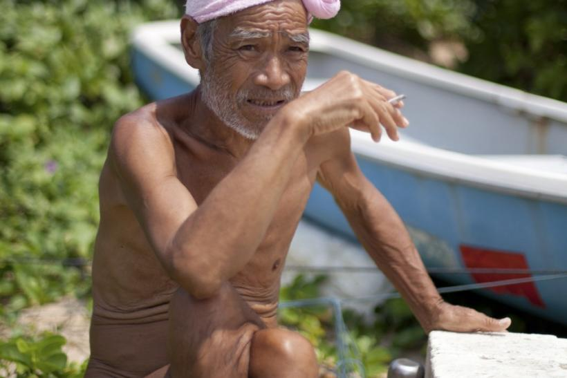 Seventy-six-year-old naked hermit Nagasaki smokes on Sotobanari island, Okinawa prefecture, Japan
