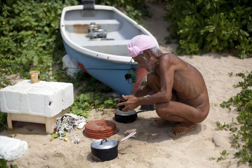 Seventy-six-year-old naked hermit Nagasaki washes untensils on Sotobanari island, Okinawa prefecture, Japan