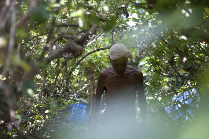 Seventy-six-year-old naked hermit Nagasaki walks through jungle on Sotobanari island, Okinawa prefecture, Japan