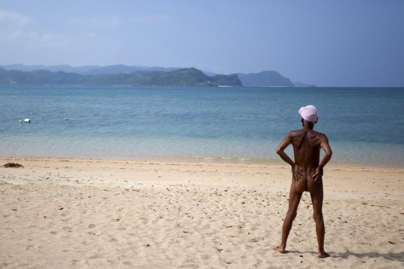 Seventy-six-year-old naked hermit Nagasaki looks at the sea from beach on Sotobanari island, Okinawa prefecture, Japan
