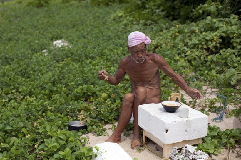 Seventy-six-year-old naked hermit Nagasaki eats a food on Sotobanari island, Okinawa prefecture, Japan
