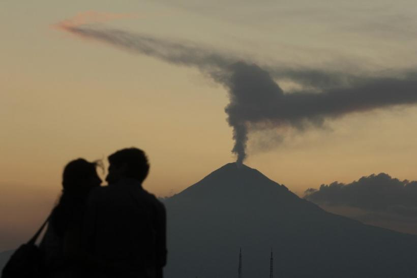 Couple embraces as the Popocatepetl volcano spews a cloud of ash and steam high into the air as seen from Puebla
