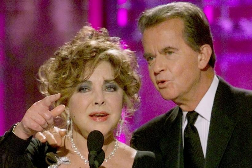 Producer Dick Clark (R) comes to the aid of Elizabeth Taylor after Taylor lost her place announcing the winner of Best Motion Picture Drama at the 58th Annual Golden Globe Awards January 21, 2001 in Beverly Hills