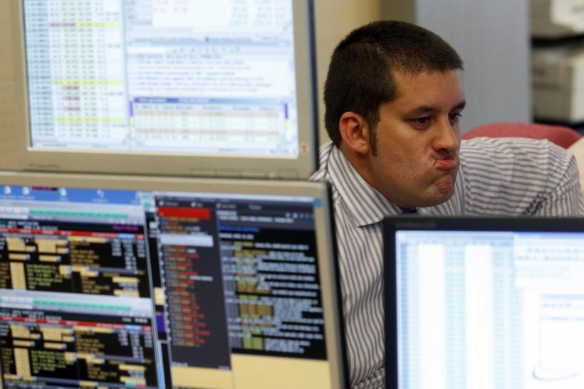 Trader gestures in front of his screens during a bond auction on a trading floor in Madrid