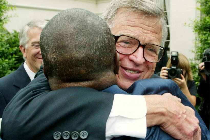 "Watergate figure Charles W. ""Chuck"" Colson, right, hugs former-Texas prison inmate Robert Sutten following a roundtable discussion with U.S. President George W. Bush on Prison Fellowship Ministries outside of the White House, June 18, 2003."