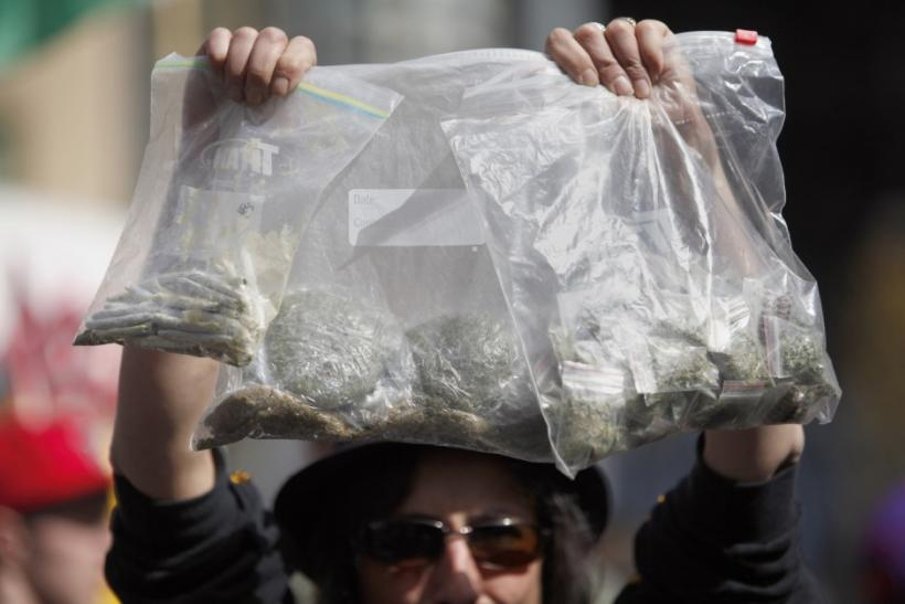A women holds up bags of marijuana for sale at the Vancouver Art Gallery