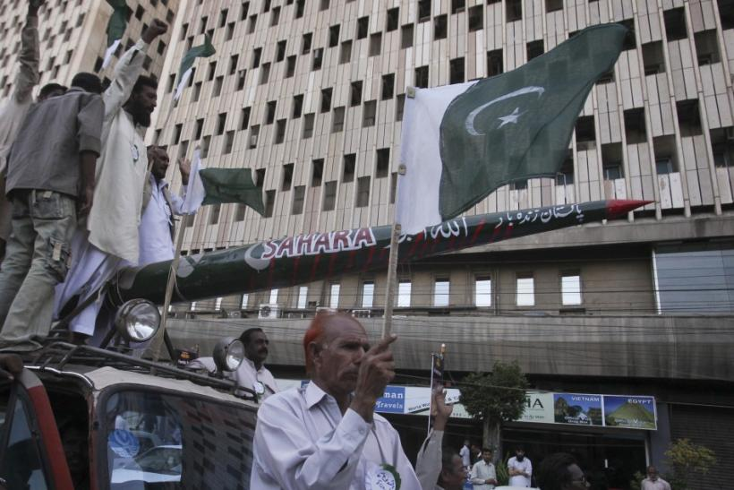 A protestor holds Pakistan's national flag as others shout slogans while transporting a mock missile during a rally in support of the Pakistan army in Karachi