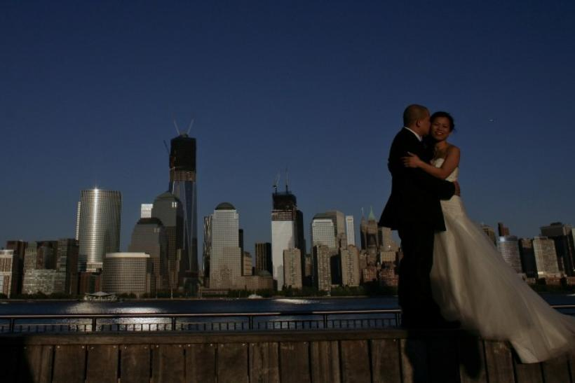 A couple, posing for their pre-wedding photographs, are back-dropped by the One World Trade Center and Manhattan skyline as seen from New Jersey