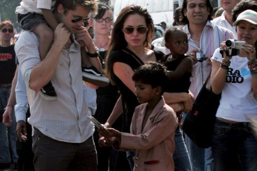 Hollywood star Pitt carries adopted son Maddox as Jolie carries adopted daughter Zahara during their stroll outside their hotel in Mumbai