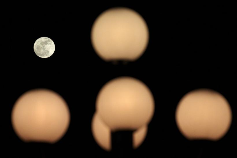 The moon is pictured behind street lamps in Lausanne