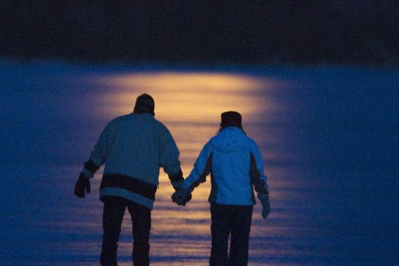 Greg Kerr and Allie Mahoney skate under a full moon on Pigeon Lake near Bobcayeon Ontario