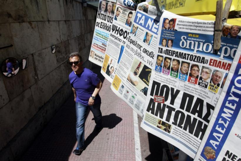 A man walks past a kiosk selling newspapers in central Athens. A trade credit crunch is threatening to affect the supply of foreign goods into that country.
