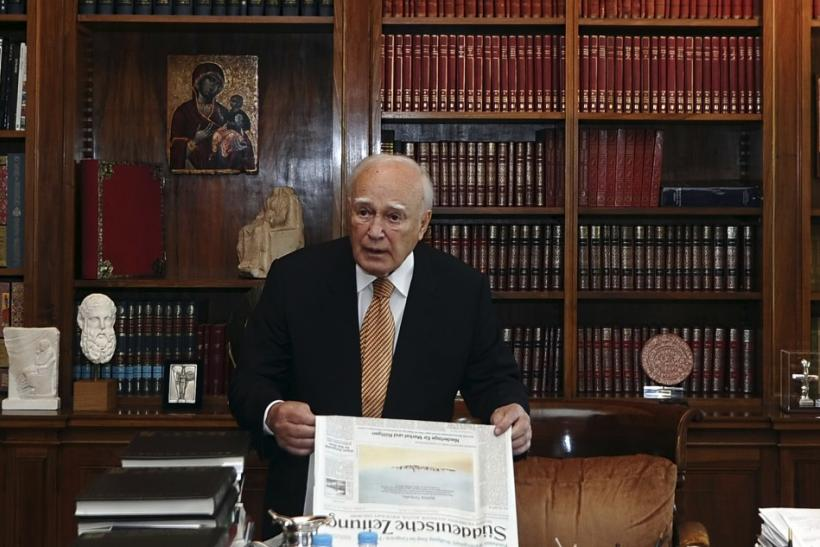 Greece's President Karolos Papoulias holds a newspaper as he stands in his office before his meeting with Evangelos Venizelos (not pictured), leader of the Socialist PASOK party, at the presidential palace in Athens May 12, 2012.