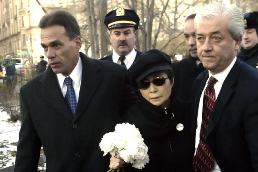 Yoko Ono (C) is escorted by police officers to a memorial to honor her deceased husband John Lennon in Central Park's Strawberry Fields in New York December 8, 2005.