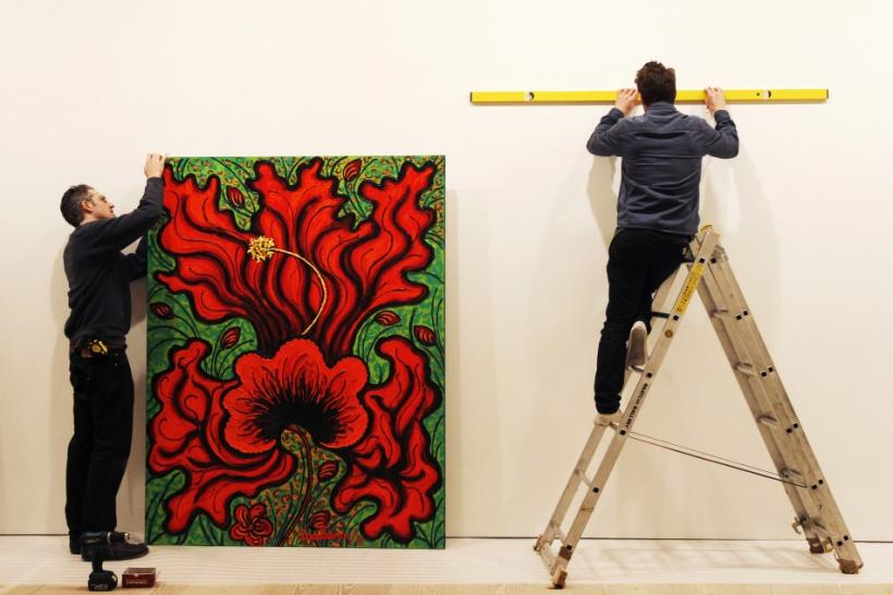 """Technicians hang artist Ana Tzarev's painting """"Love (Hibiscus)(Garden La Fleur du Cap)"""" at the Saatchi Gallery in London May 17, 2012. Thione hopes his Artify It service will mark a major departure from the traditional gallery setting"""