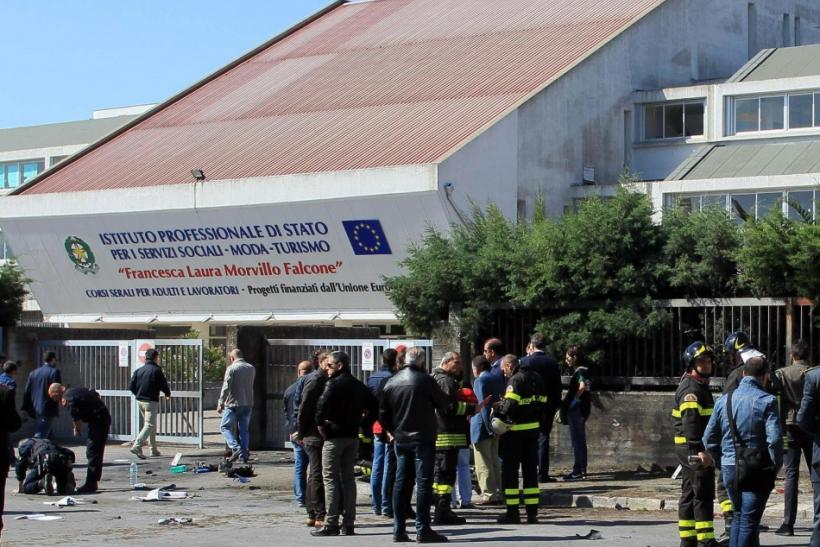 Italian policemen and fire fighters inspect in front of the school where a bomb exploded in the southern Italian town of Brindisi