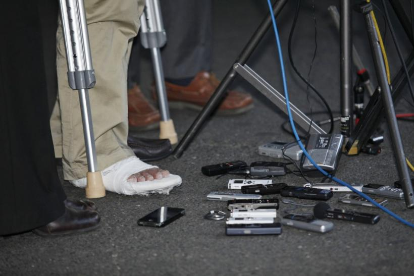 The injured foot of blind Chinese dissident Chen is pictured next to recording equipment from the media as he speaks during his arrival in New York