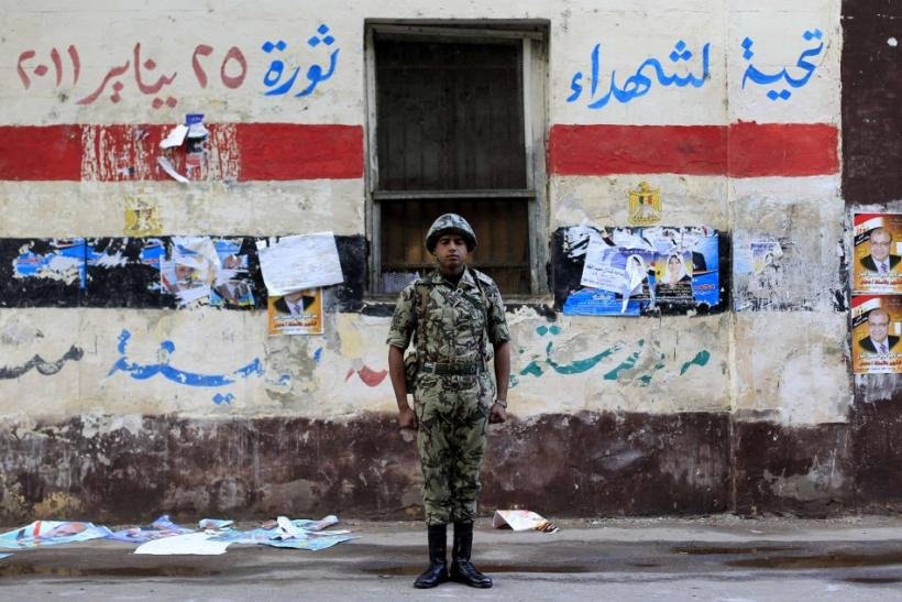 An Egyptian soldier stands guard in front of a polling station in Cairo November