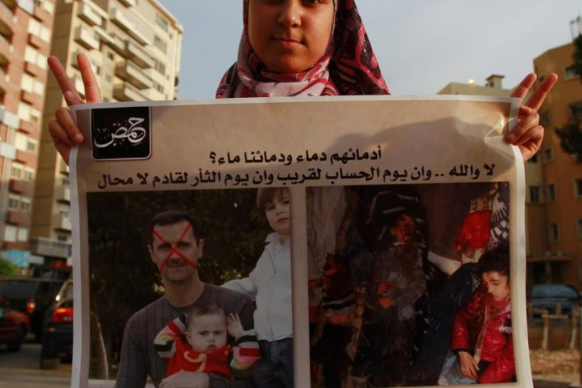 A Syrian refugee girl poses with a placard depicting Syria's President Bashar al-Assad with his children (L) and children who protesters say were killed by government security forces during a protest in Tripoli, northern Lebanon, May 26, 2012, agains