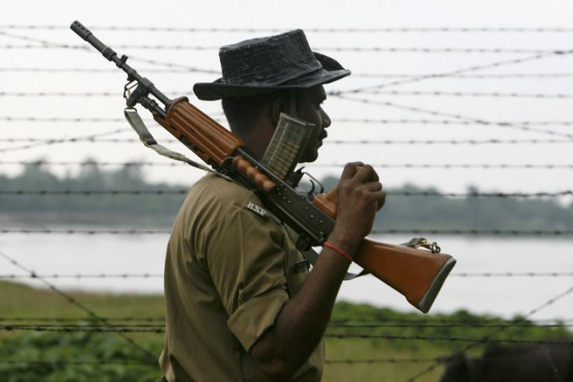 Indian BSF soldier keeps watch along the fenced border with Bangladesh