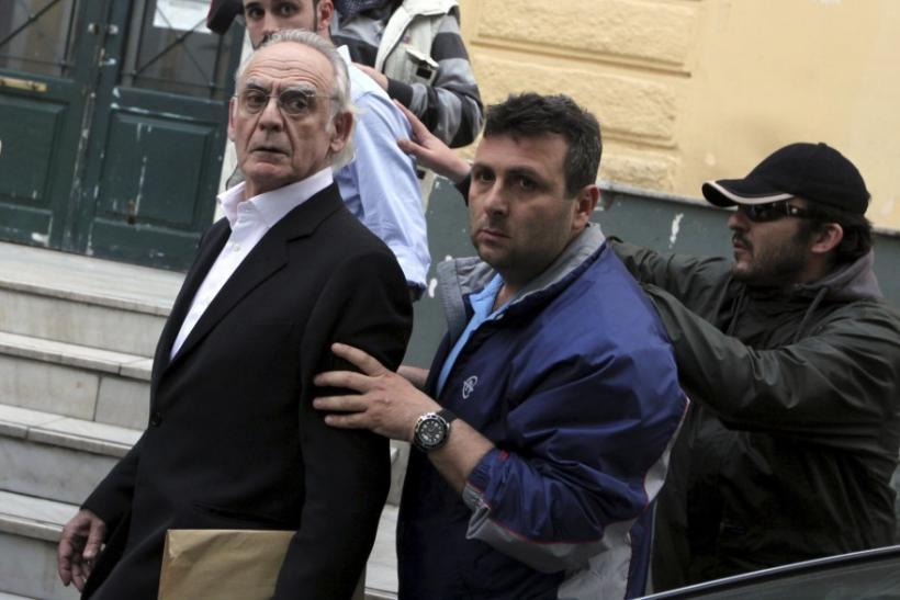 Former socialist minister Akis Tsohatzopoulos ,72, is escorted by plainclothes policemen as he is led to jail in Athens
