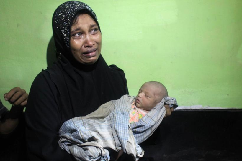 Amena Akter, a Rohingya from Myanmar, cries as she holds her 6-day-old son, Sangram, in the office of the Bangladesh Coast guard in Teknaf