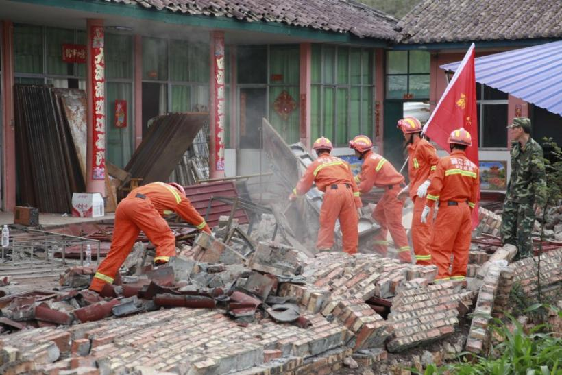 Firemen clean up debris at a factory which was damaged by an earthquake in Ninglang county