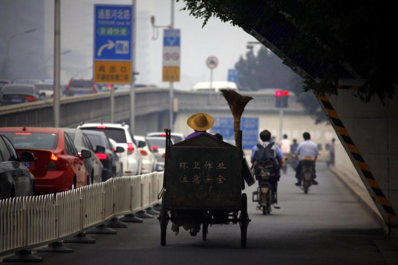 A cleaner rides his tricycle down a side-road as cars sit in a traffic jam along a main road in central Beijing