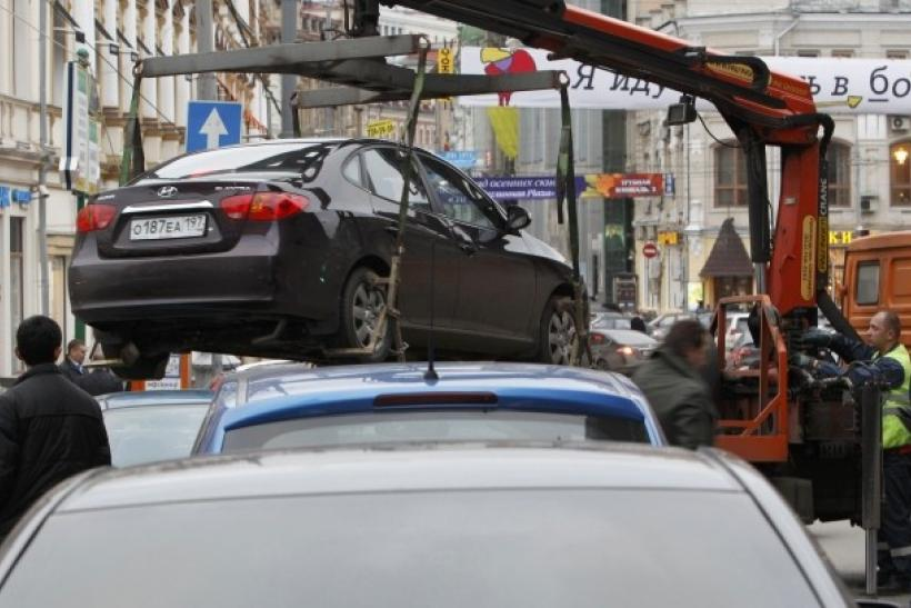 File photo of city authorities lifting a car parked on a pedestrian crossing before towing it away in Moscow. This is what I'm always afraid will happen to my car in New York City. I have no reason to suspect that.