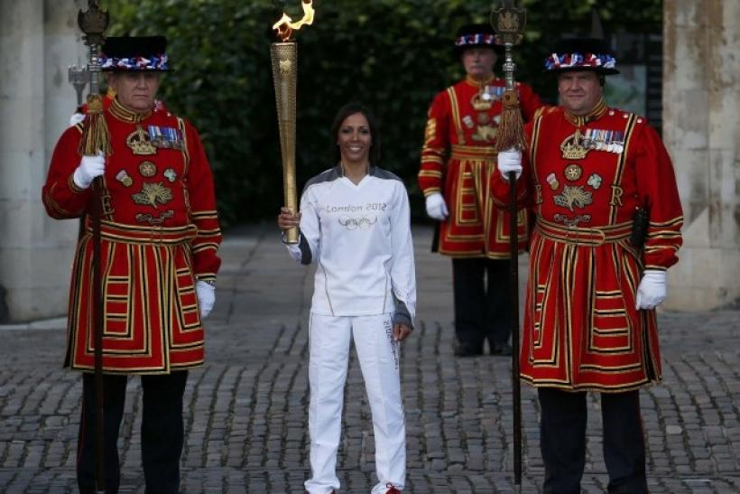 Britain's Holmes holds the London 2012 Olympic torch as she poses with Yeoman Warders at the Tower of London