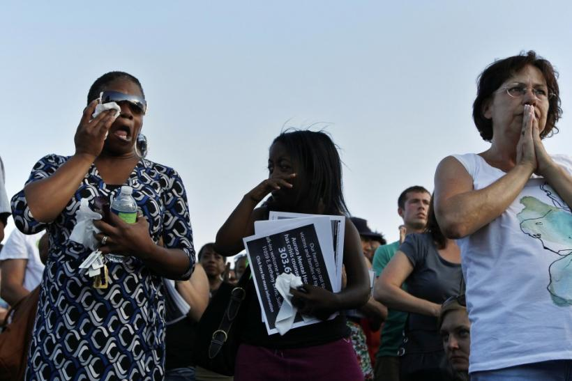 People pray during a vigil for victims behind the theater where a gunman opened fire in Aurora, Colorado