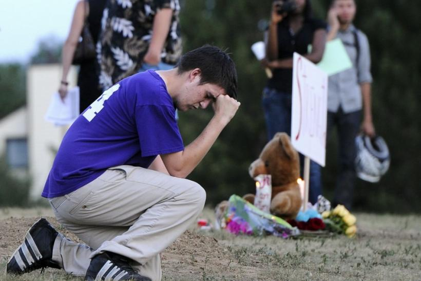 A man prays during a vigil for victims behind a theater where a gunman opened fire in Aurora, Colorado.