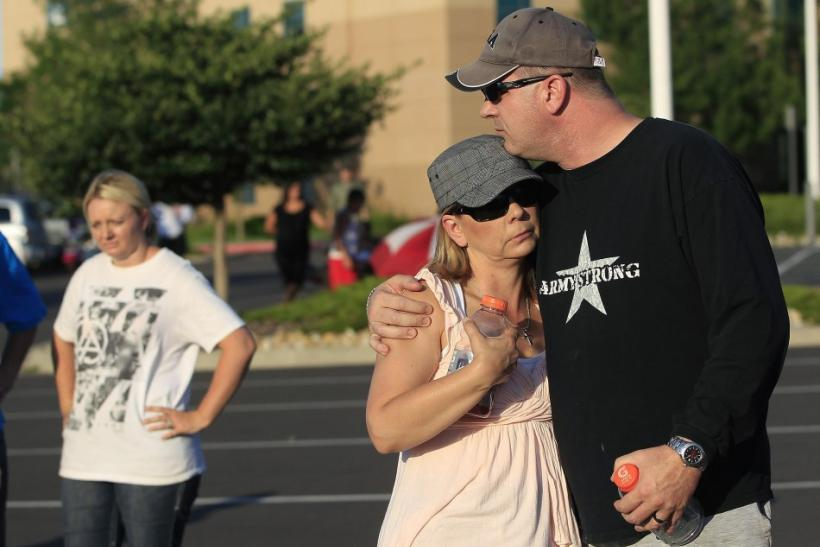 A couple embraces before a vigil for victims behind the theater where a gunman opened fire in Aurora, Colorado