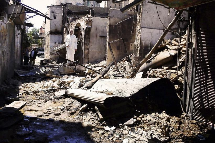 People look at damage at al-Midan neighbourhood in Damascus July 23, 2012.