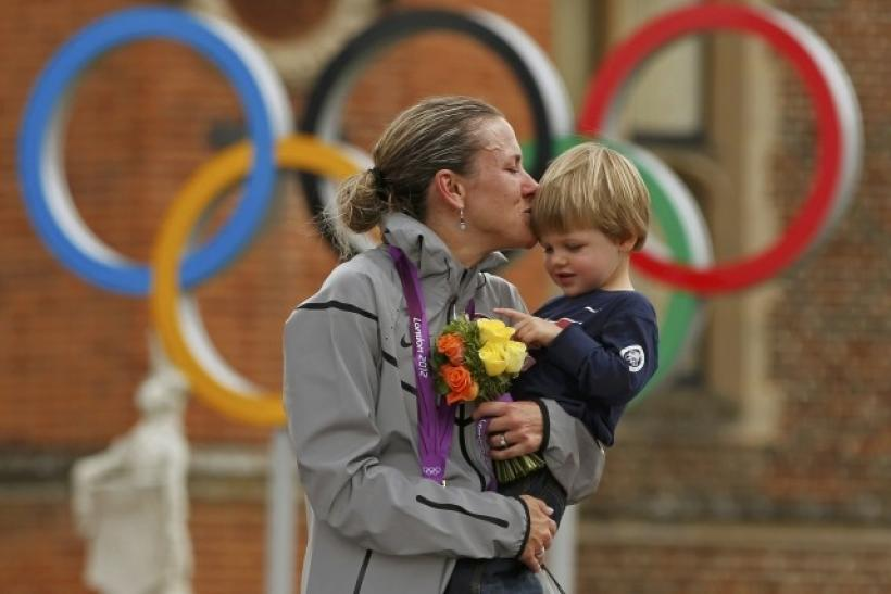 Gold medallist Kristin Armstrong of the U.S celebrates with her son Lucas William Savola on the podium during the victory ceremony of the women's cycling individual time trial at the London 2012 Olympic Games