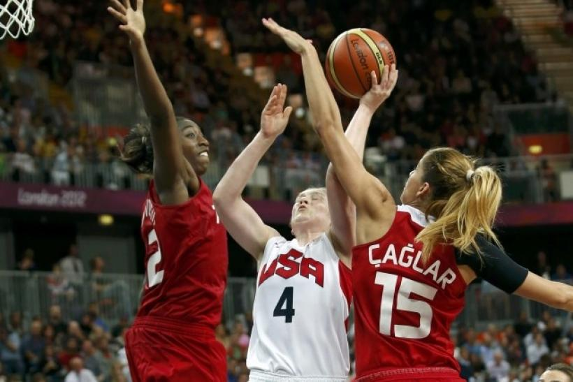 Whalen of the U.S. goes between Turkey's Hollingsvorth and Caglar during their Women's preliminary round group A basketball match at the Basketball Arena during the London 2012 Olympic Games