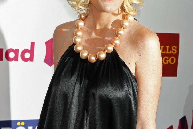 Tori Spelling loves to show her expanding belly in fashionable bikinis